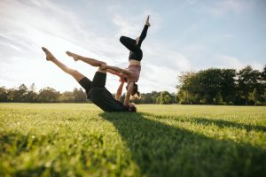 Junge Frau beim Yoga auf Gras