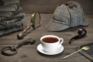 Sherlock Holmes Concept. Private Detective Tools On The Wood Table Background. Deerstalker Cap, Magnifier, Key, Cup, Notebook, Smoking Pipe.