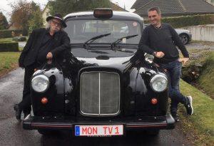 """In der Eifel im Original London-Taxi unterwegs für sein Videoformat """".. auf die Socken machen"""" bei MonTV, hier mit Senderchef Dirk Neuss."""